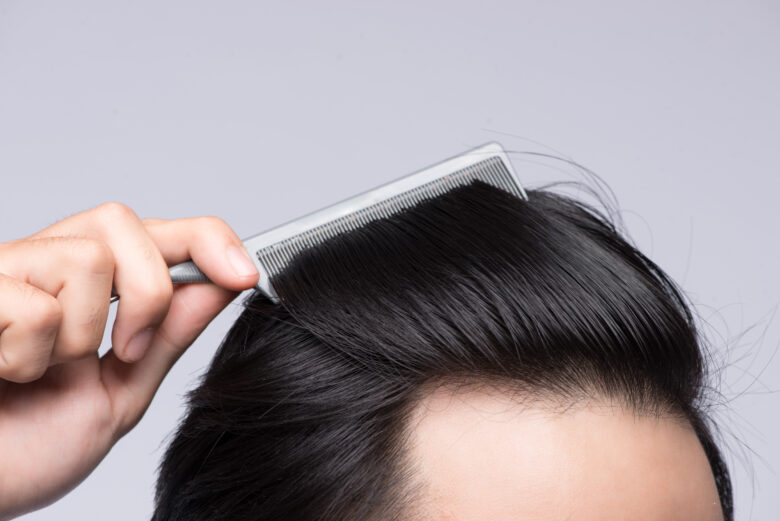 Close up photo of clean healthy man's hair. Young man comb his hair