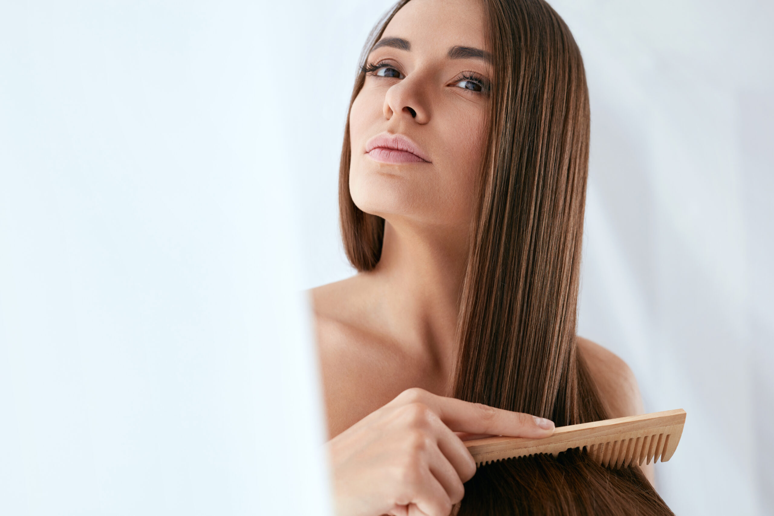 Beauty Hair Care. Beautiful Woman Combing Long Natural Hair