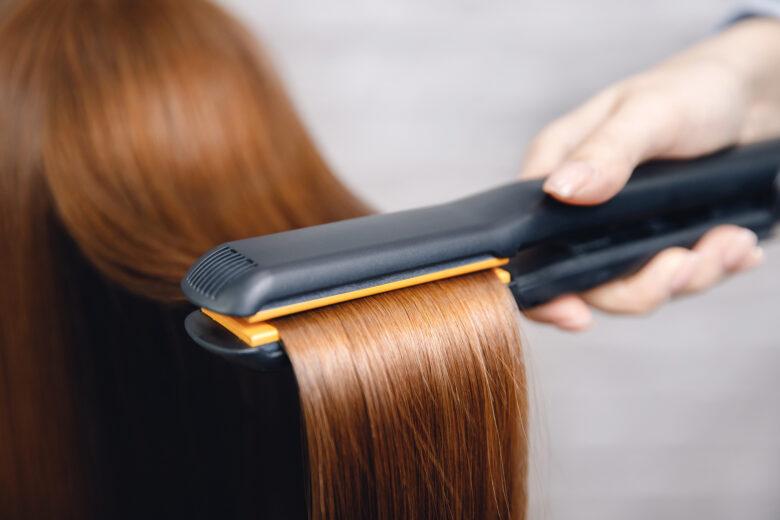 Hair straightening iron in beauty salon