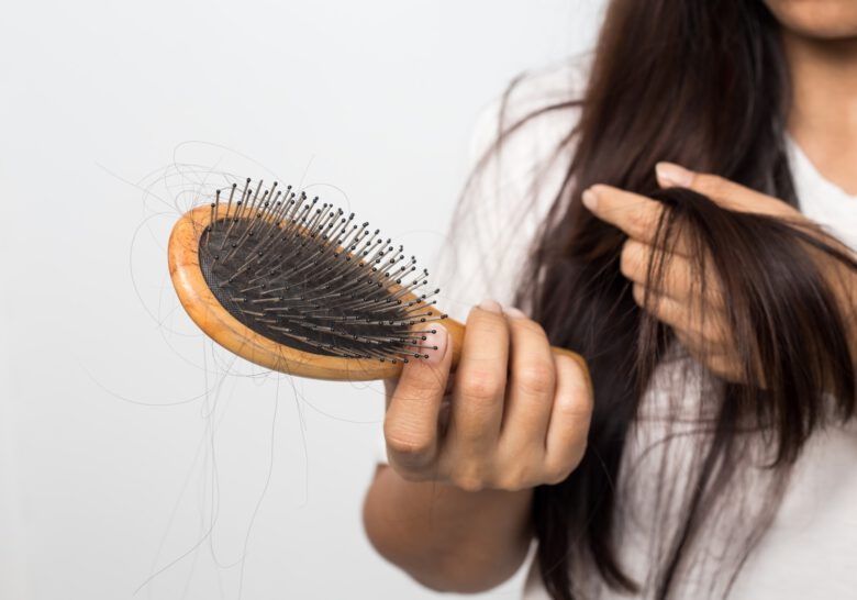 young woman worried about hair loss on a white background